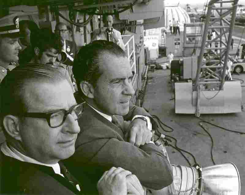 President Richard Nixon (right) and NASA Administrator Thomas O. Paine, aboard the USS Hornet, watch the Apollo 11 astronauts walk from the recovery helicopter to a quarantine facility on the ship on July 24, 1969.