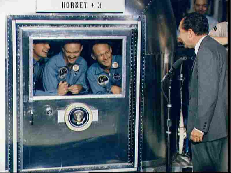 Confined to a quarantine chamber aboard the USS Hornet after returning from the moon, Apollo 11 astronauts Neil Armstrong (from left), Michael Collins and Edwin Aldrin speak to President Richard Nixon on July 24, 1969.