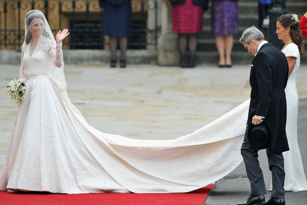 Kate Middleton waves to the crowds as her sister, Pippa, holds her dress next to her father, Michael, before entering Westminster Abbey.