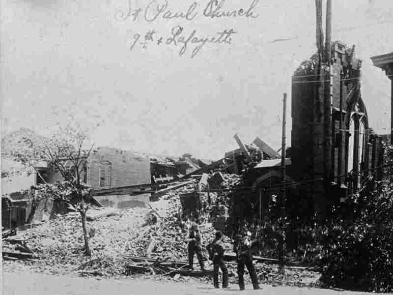 People stand near a demolished church in St. Louis after it was hit by a tornado that killed hundreds of people on May 27, 1896.