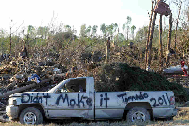 A damaged truck is covered in graffiti in a tornado-ravaged area near Rainsville, Ala., Thursday. At least 32 people died in Dekalb County, when the tornado struck on Wednesday.