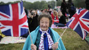 A fan holds British Union Jack flags as people gather to watch the wedding of Britain's Prince William and Kate Middl