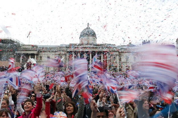 Well-wishers wave flags in Trafalgar Square to celebrate the wedding of Prince William and Kate Middleton on Friday.  (AP)