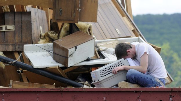 Andy Page cries as he sits with his cat, Ellie, placed in a pet carrier, in his storm-demolished apartment in Trenton, Ga., on Thursday. Page has several cats, and Ellie was the last one he was looking for.