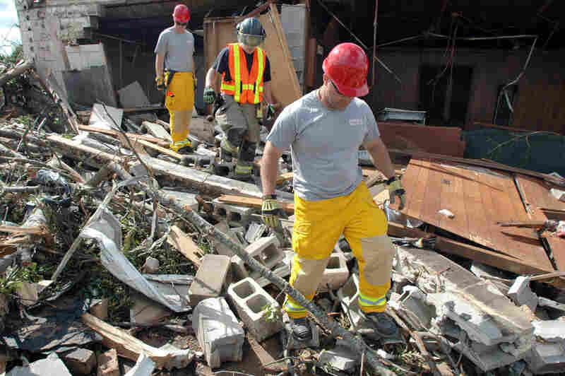 Firefighters search the rubble of a home in the Alberta City section of Tuscaloosa, Ala., on Thursday.