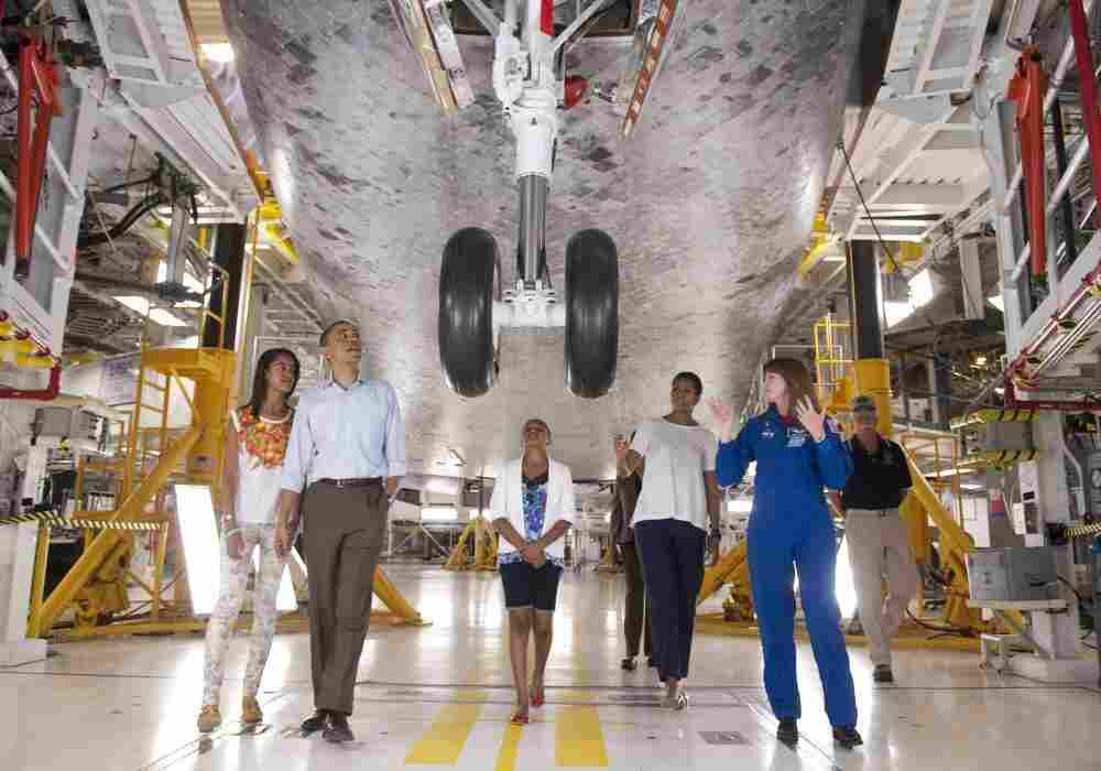 Astronaut Janet Kavandi, director of Flight Crew Operations for Johnson Space Center, leads President Barack Obama, First Lady Michelle Obama and daughters Sasha and Malia, as they view the front landing gear of Space Shuttle Atlantis.