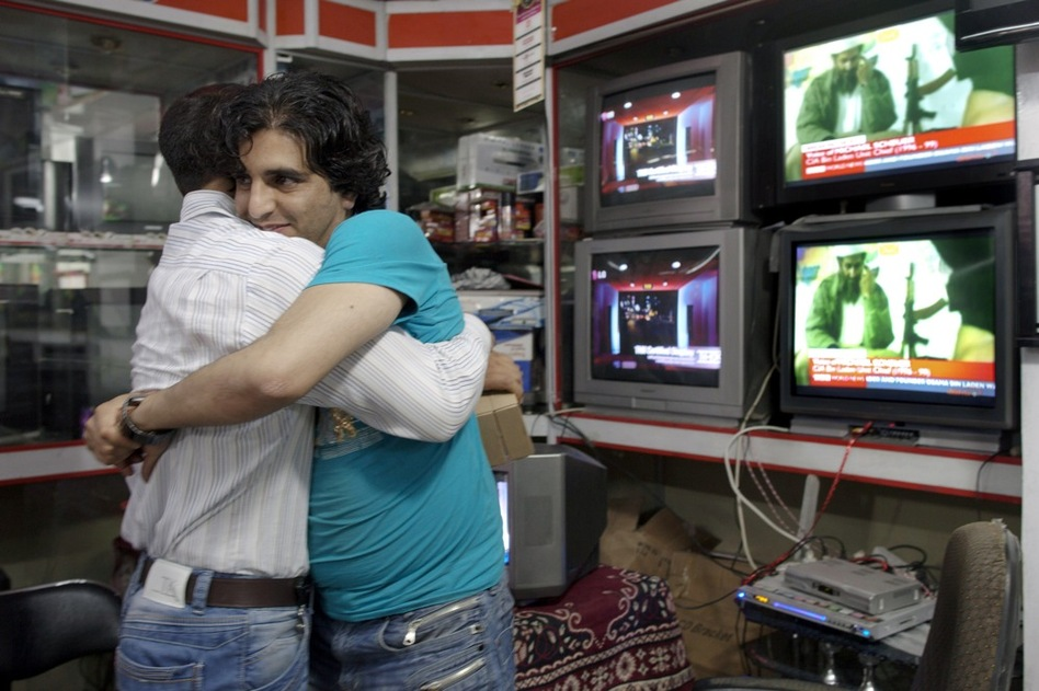 Afghan men hug each other while watching the news of bin Laden's death. Bin Laden was killed in a firefight with U.S. forces at a compound in Abbottabad, Pakistan, early Monday.  (Getty Images)