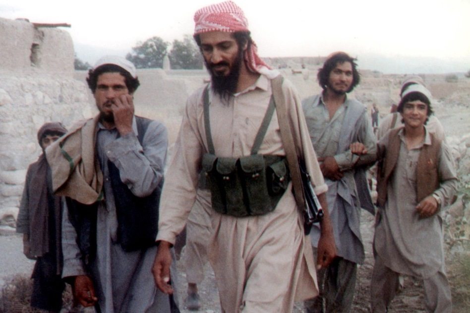 Bin Laden (center) walks with Afghanis in Jalalabad, Afghanistan, in 1989. The news of his death sent the world into celebration and protest.  (Getty Images)