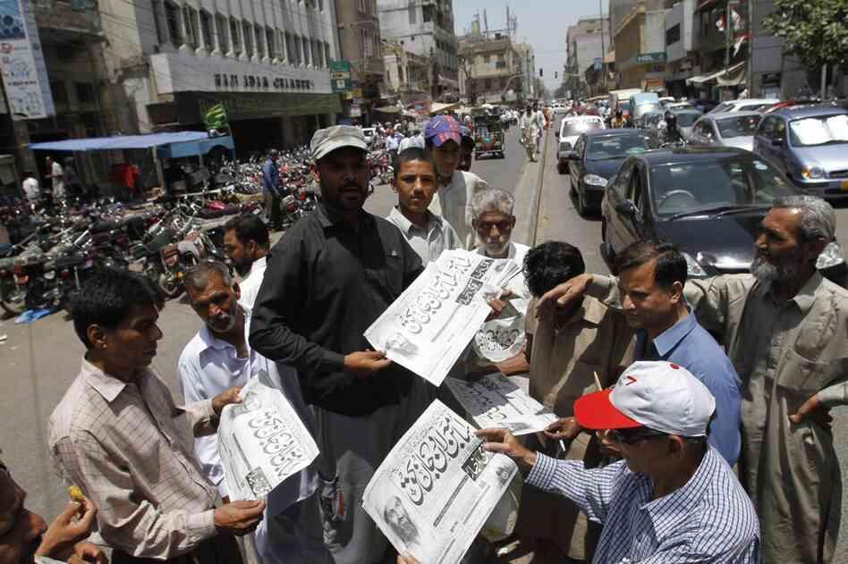 Men in Karachi, Pakistan, buy newspapers reporting the killing of bin Laden.