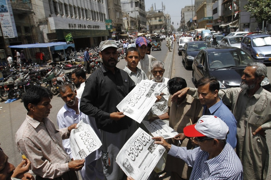 Men in Karachi, Pakistan, buy newspapers reporting the killing of bin Laden.  (AP)