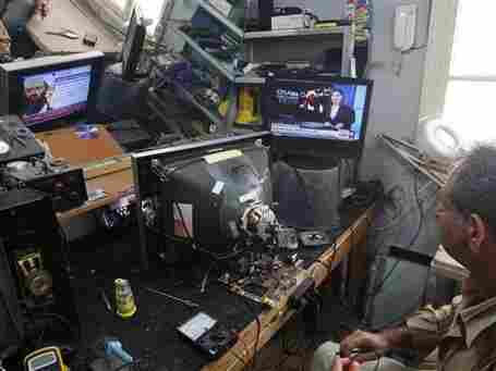 A man fixes televisions as he watches a TV broadcast on the death of Osama bin Laden in his workshop in the southern port city of Sidon, Lebanon, on Monday.
