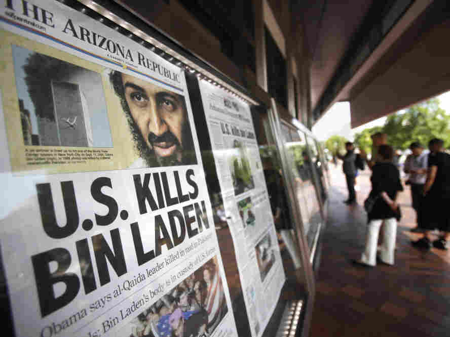 People look at a display of newspaper front pages at the Newseum in Washington on Monday. Millions of Americans received the historic news not from Obama's televised news briefing Sunday night, but by text message, email and alerts from Twitter and Facebook, in many instances before the details had been reported by traditional media.