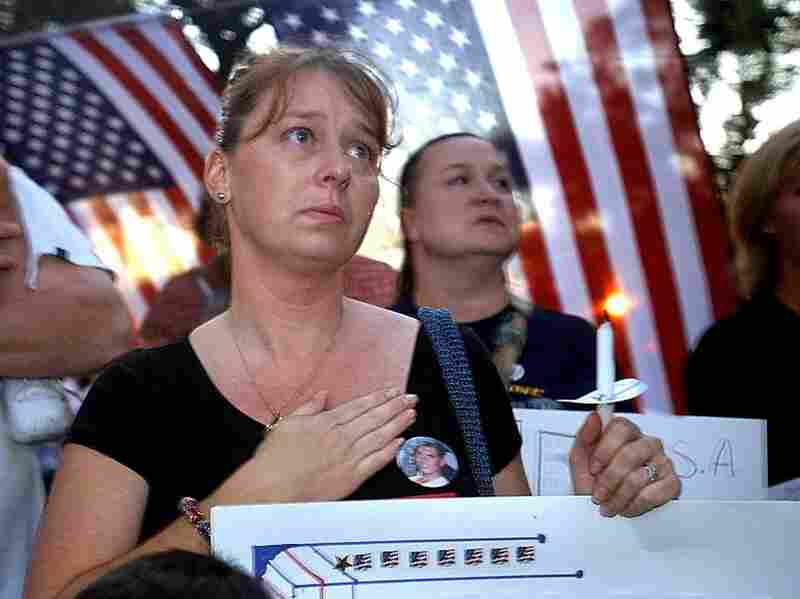 The wife of a victim of the attacks on the World Trade Center attends a candlelight vigil in New York City in 2002.