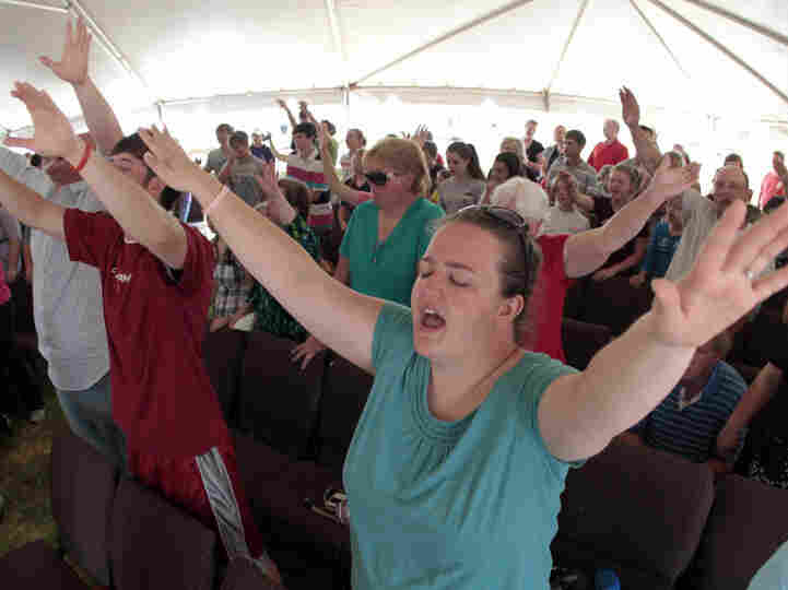 Brianne Knowles prays during a church service in Hackleburg, Ala., on Sunday. The church was heavily damaged in last Wednesday's tornado, requiring parishioners to use a tent.