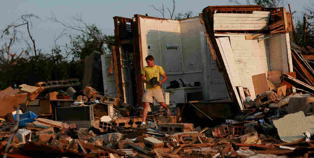 University of Alabama student Clayton Farr gathers his belongings from his destroyed home in Tuscaloosa, Ala. The twisters mostly avoided the main campus, but many students and staff living off campus are dealing with devastation.