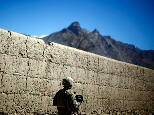 A soldier on patrol in Charkh.  Until Bravo Company took control of both sides of the river, insurgents would often lob homemade hand grenades from behind the mud-brick orchard walls.