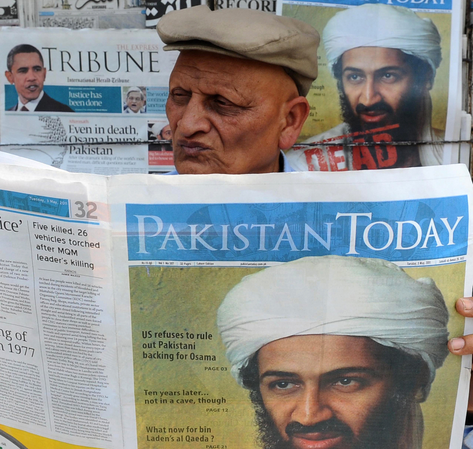 A Pakistani man reads a newspaper with the front page displaying news of the death of Osama bin Laden at a stall in Lahore on May 3.