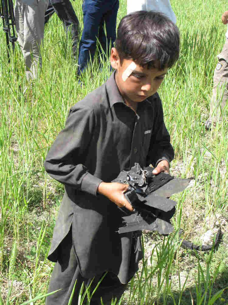 A boy collects small pieces of wreckage that were strewn in the area  following the U.S. raid that killed bin Laden.