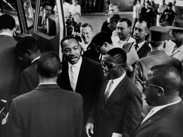 Dr. Martin Luther  King Jr. sees off a group of Freedom Riders as they board a bus for Jackson, Miss., on May 24, 1961.