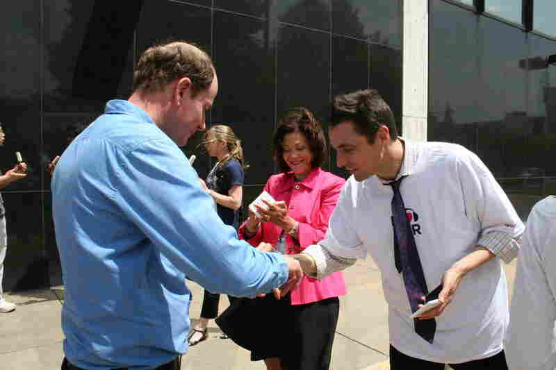 ATC executive producer Christopher Turpin and host Michele Norris give out hand stamps to staffers.