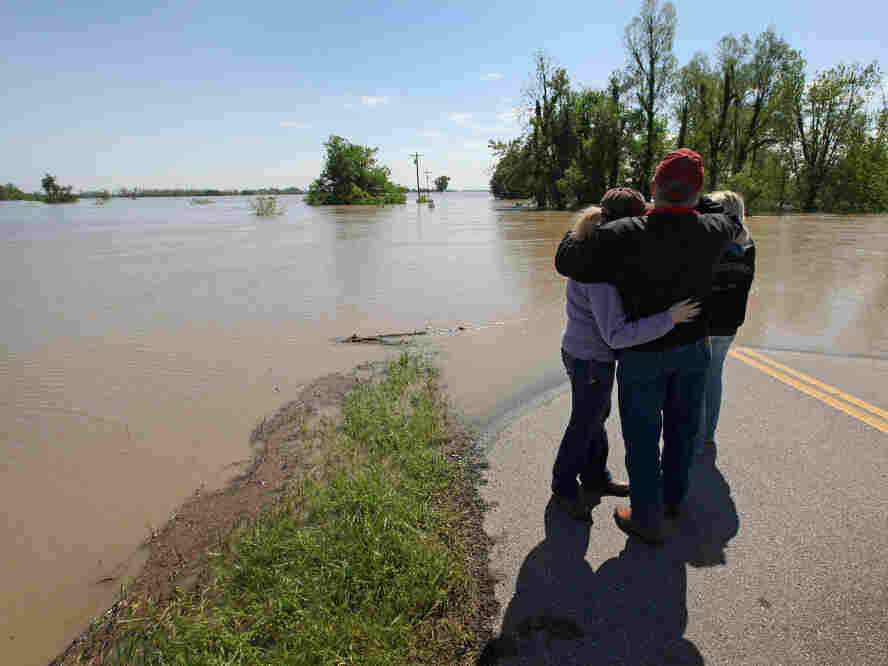 Roy Presson (C) embraced his daughters Catherine (L) and Amanda on Tuesday as they stood on the edge of State Highway HH looking out at their family farm in Wyatt, Mo. The Presson home and 2,400 acres of land that they farmed was flooded when the Army Corps of Engineers blew a massive hole in a levee at the confluence of the Mississippi and Ohio Rivers to help save the town of Cairo, Ill.