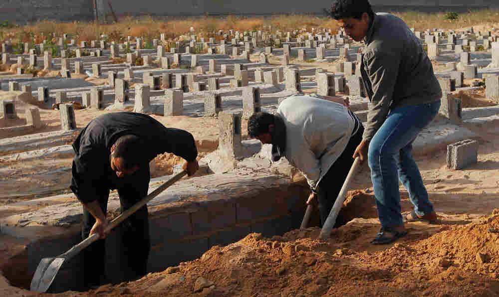 Gravediggers burn a civilian victim in Misrata, Libya, on April 19, 2011.