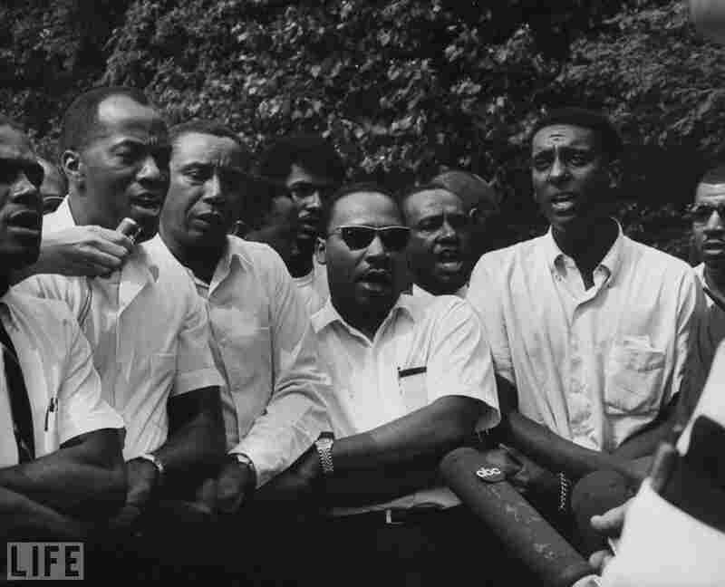 King (center) and his colleagues speak to the press at a voter-registration march from Memphis, Tenn., to Jackson, Miss., in 1966.