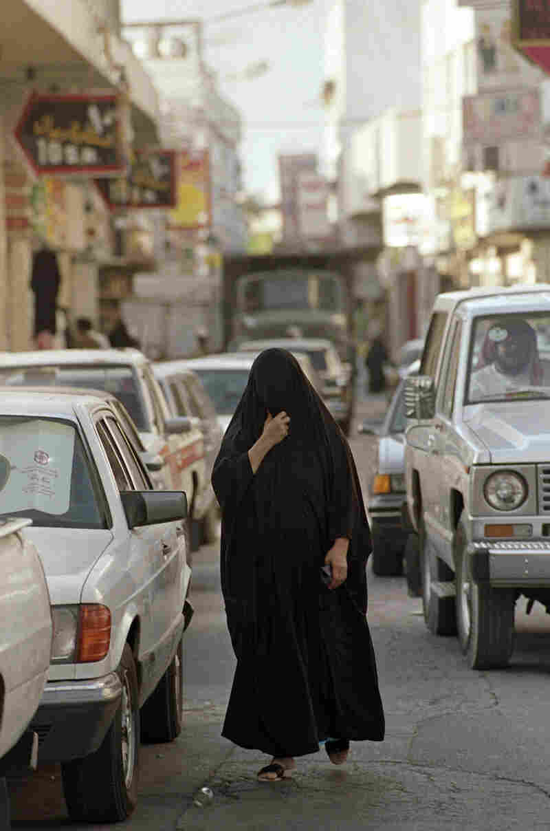 A Saudi woman crosses in front of several automobiles in a marketplace on Sept. 16, 1990, in Dammam. Women in Saudi Arabia are not allowed to drive, have little say in matters of marriage and divorce, and cannot travel without a letter of permission from their male guardian.