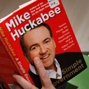 Huckabee signs a copy of his new book, A Simple Government: Twelve Things We Really Need from Washington (and a Trillion that We Don't!), at the National Press Club, February 2011 in Washington.