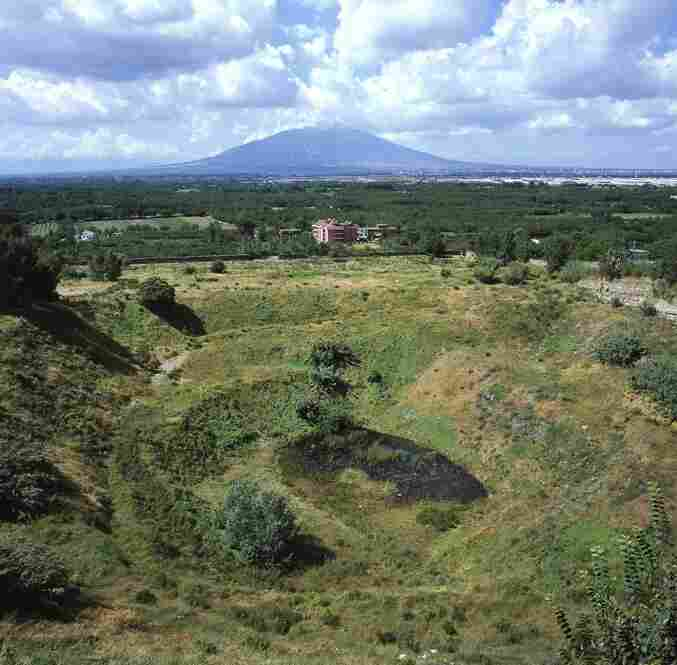 Mount Vesuvius is seen beyond a natural quarry known to have been used as an illegal toxic waste dumping ground by Italian Mafia organizations. Once the waste is dumped, it is quickly absorbed into the region's groundwater and irrigation canals.