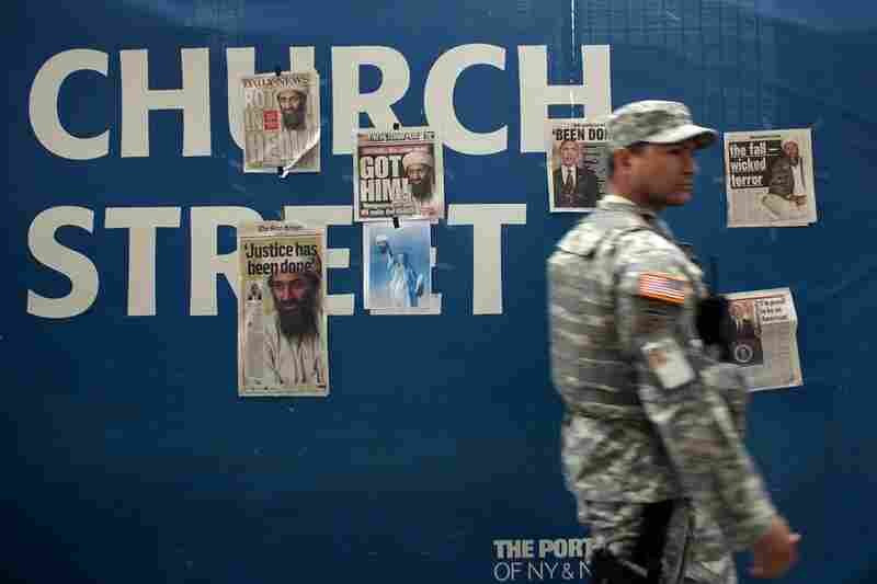 A U.S. soldier walks by newspaper clippings on a wall at ground zero heralding the death of Osama bin Laden, May 2.
