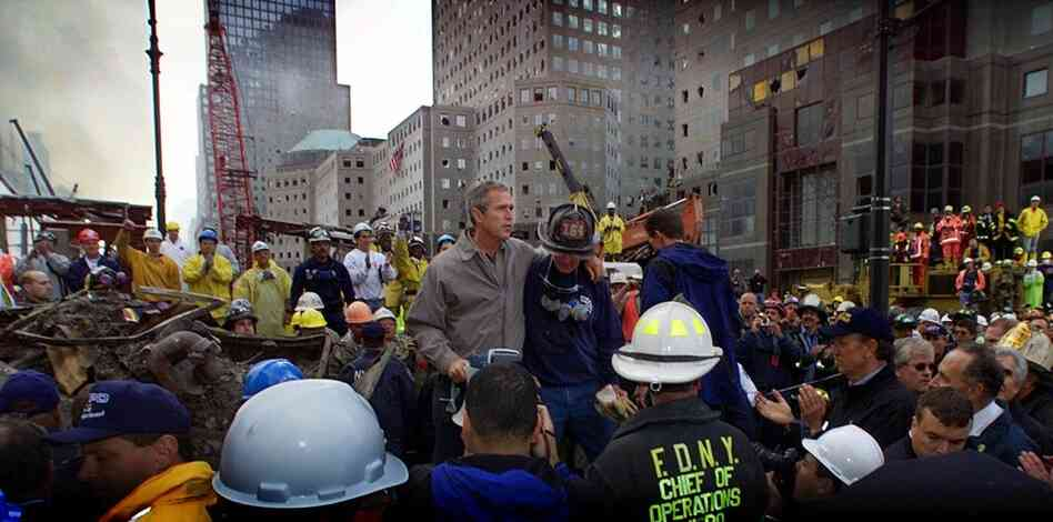 President Bush, surrounded by firefighters, tours the devastation at the center on Sept. 14, 2001.