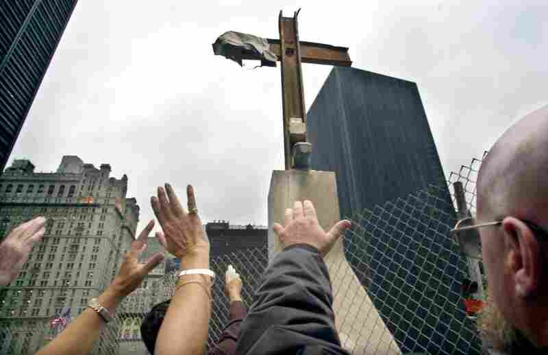 The Rev. Brian Jordan (with bottle) applies holy water to a steel beam cross during its rededication at the World Trade Center site in New York, Oct. 3, 2002.