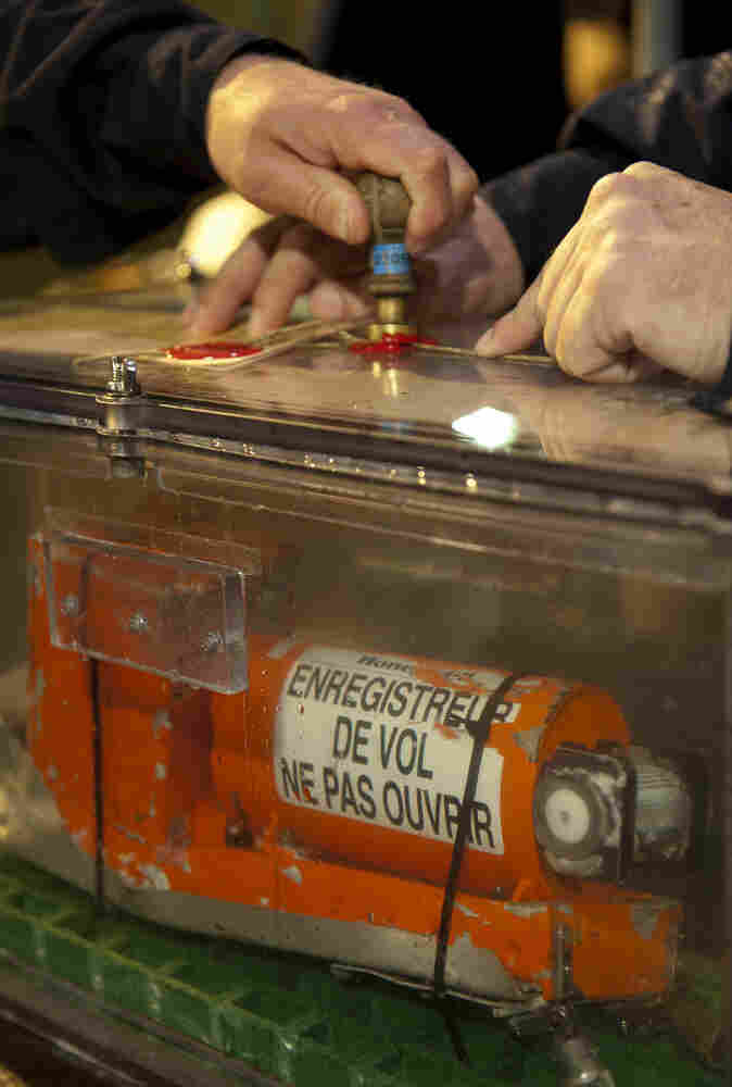 Investigators hold the sealed flight data recorder recovered from the crashed Air France Flight 447.