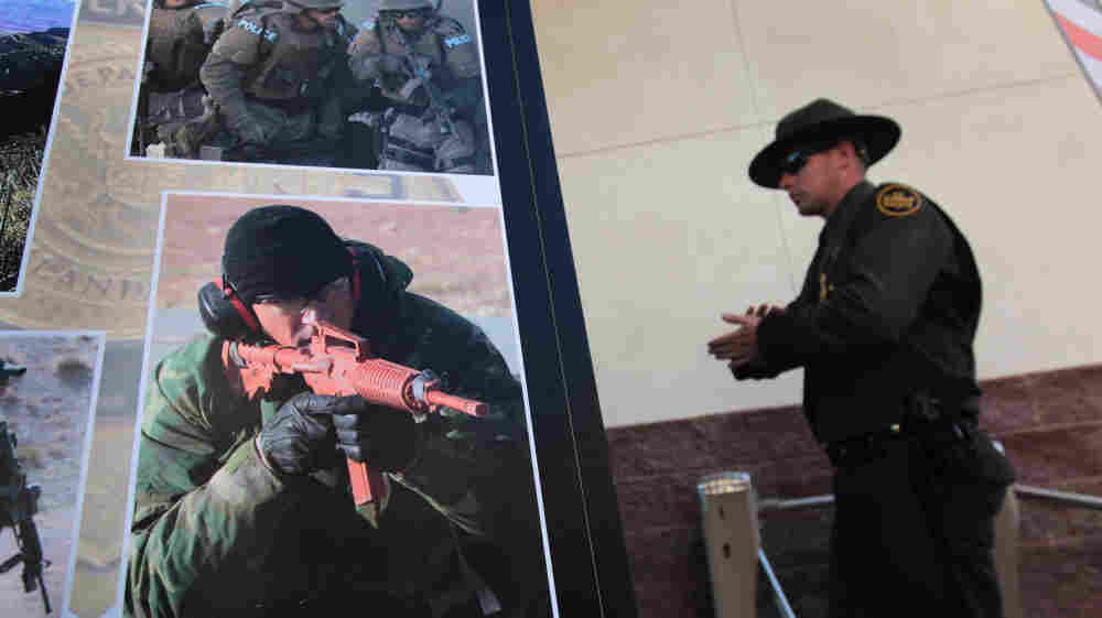 A U.S. Border Patrol agent walks past photos of slain fellow agent Brian Terry, a Marine Corps veteran, during a memorial service on Jan. 21, 2011, in Tucson. Terry was killed during a Dec. 14 shootout near the U.S.-Mexico border. Thousands of Border Patrol agents and law enforcement officers from across Arizona turned out for the memorial.