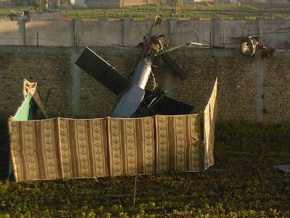 A photo taken by a local resident shows the wreckage of a helicopter next to the wall of the compound where Osama bin Laden was shot and killed.