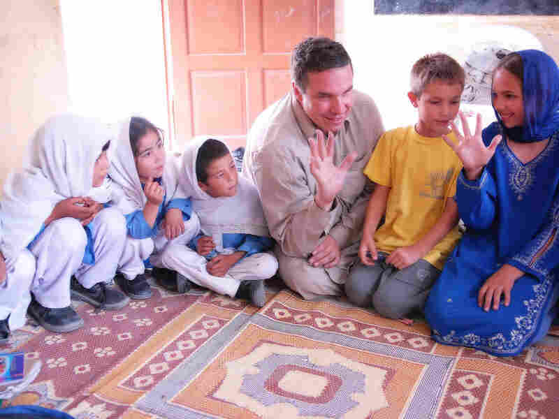 Three Cups of Tea author Greg Mortenson, with son Khyber and daughter Amira, sit with students at the Gultori War refugee school in Pakistan. A 60 Minutes report questioned some of the stories Mortenson tells in the book and his charity's use of funds.