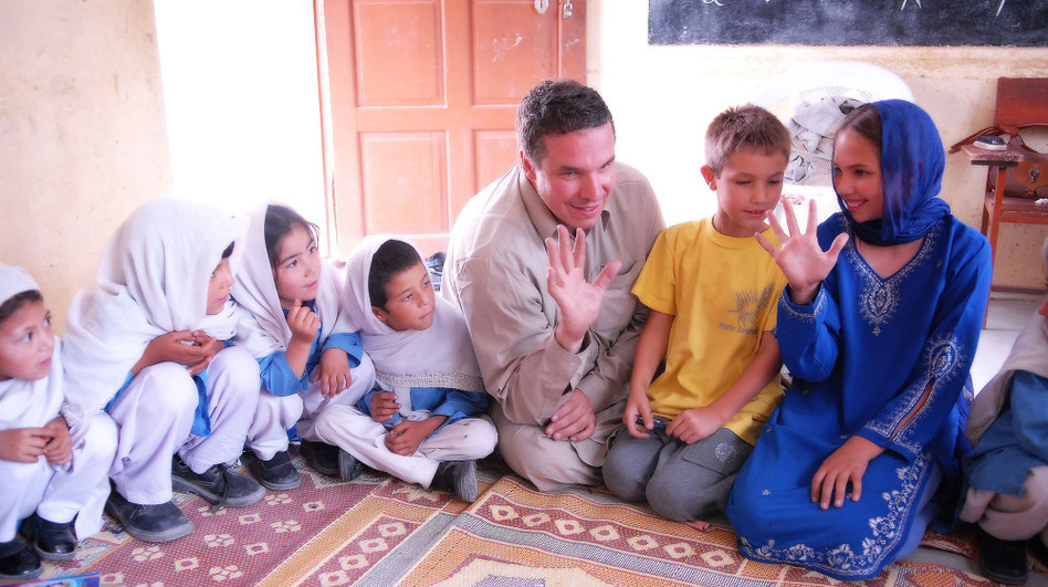 "<em>Three Cups of Tea</em> author Greg Mortenson, with son Khyber and daughter Amira, sit with students at the Gultori War refugee school in Pakistan. A <a href=""http://www.youtube.com/watch?v=XhAb37yZ0o0&feature=player_embedded"">60 Minutes</a><em> </em>report questioned some of the stories Mortenson tells in the book and his charity's use of funds."
