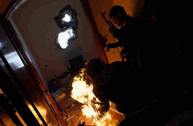 A rebel fighter rolls a burning tire into a room where government loyalist troops are hiding.