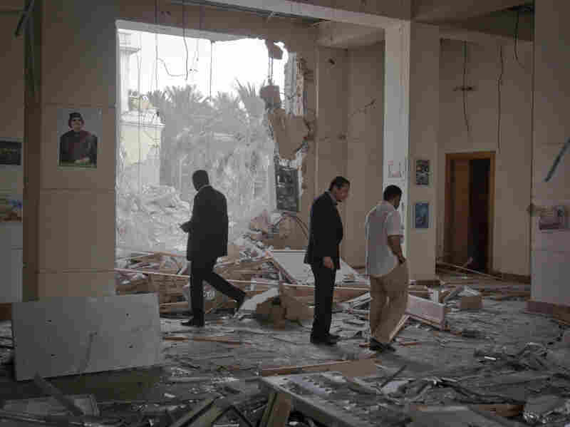 In this photo taken on a government-organized tour, officials inspect damage at the scene of an airstrike in Tripoli, Libya, on April 30.