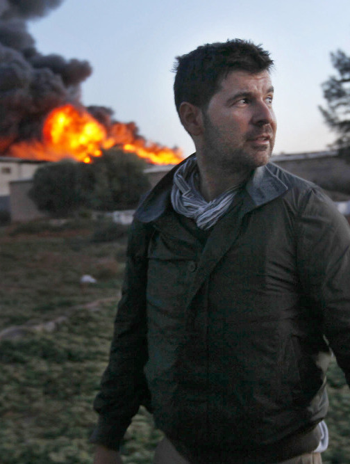 Chris Hondros stands in front of a burning building in Misrata, Libya, on April 18. Hondros, 41, died April 20, after being seriously wounded while on assignment in Misrata.