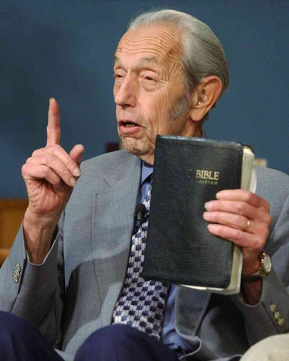 Harold Camping speaks, holding a Bible, during his live television broadcast in 2002.