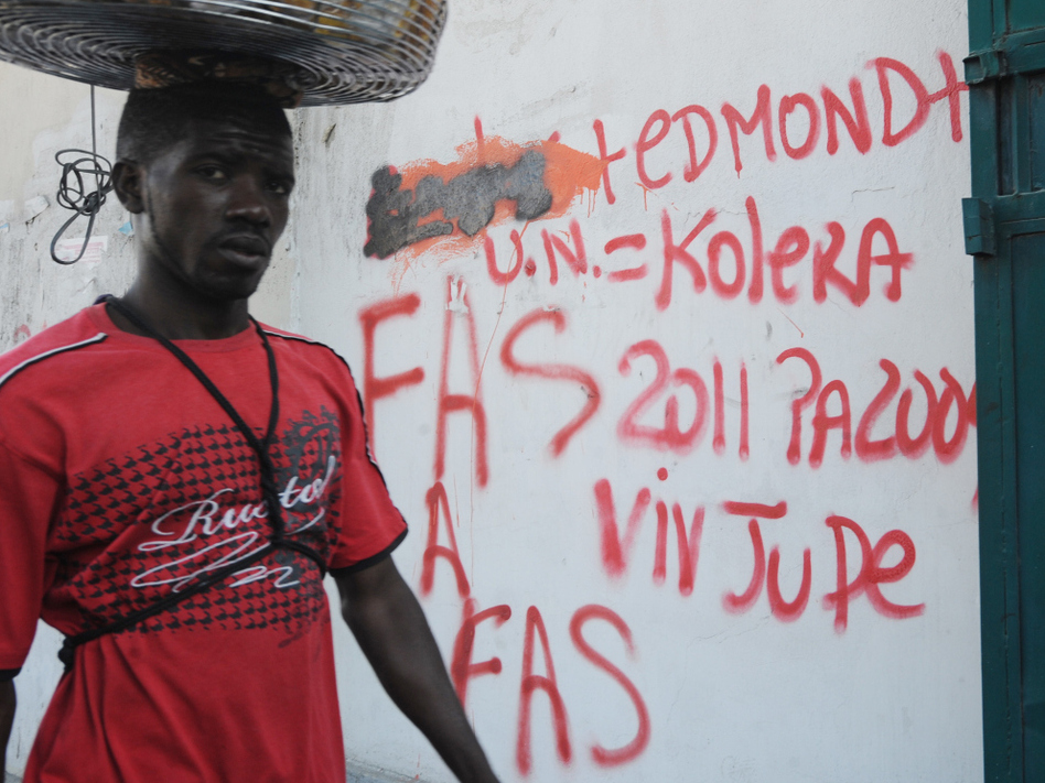 A man walked by a Port-au-Prince wall in February covered with anti-U.N. graffiti that equates the organization with cholera. (AFP/Getty Images)