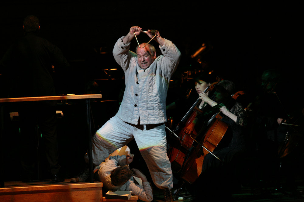 "David De Christopher, center, with Pete Cross, (lying down), performing ""Every Good Boy Deserves Favour"" by Tom Stoppard and Andre Previn during the Toledo Symphony with Stefan Sanderling, Principal Conductor during the second half of the Spring for Music festival at Carnegie Hall in Manhattan, New York on May 07, 2011."