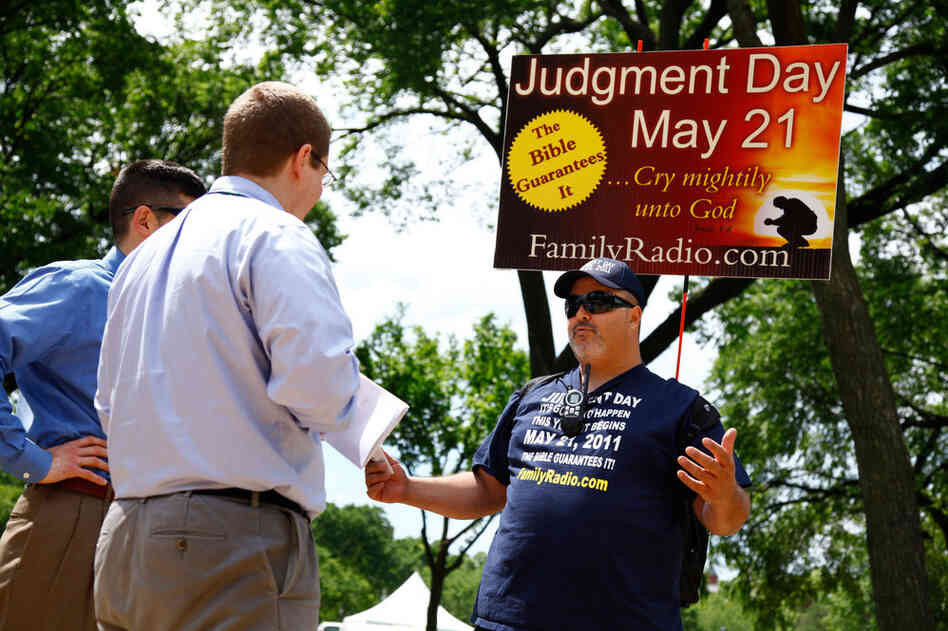David Liquori (right) talks to two men on National Mall in Washington, D.C., on Friday. The Long Islander has been speaking about Judgment Day for 23 years. His passion for the message resulted in the end of his marriage because his wife had different views. His 12-year-old son is skeptical of his father's views, and Liquori worries about him. He isn't sure how he plans to spend May 21, but he ...