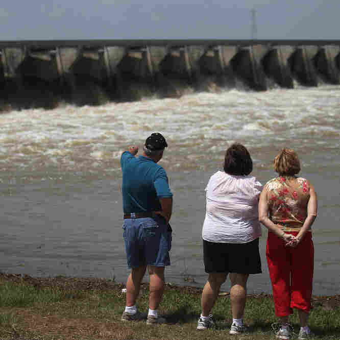 People look on as water from the rising Mississippi River is released through the Bonnet Carre Spillway in Norco, Louisiana. The Army Corps of Engineers began redirecting part of the Mississippi River through the spillway today to lower river levels and reduce pressure on levees.