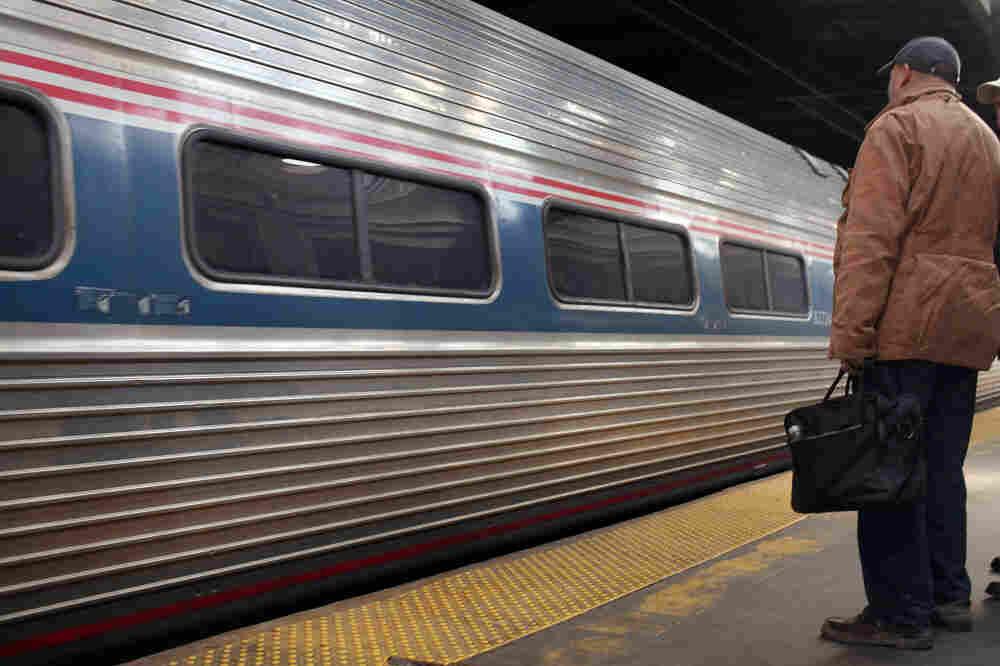 A commuter waits for an Amtrak train at Newark Penn Station.