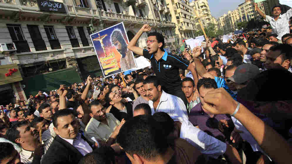 """Egyptian Copts — one holding a banner with a picture of Jesus Christ and writing in Arabic reading """"Christ, our God, is alive"""" —  demonstrate in Cairo after sectarian violence over the weekend left at least a dozen dead."""