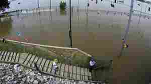 People take a look at Mississippi River floodwaters at the base of Beale Street in Memphis, Tenn.