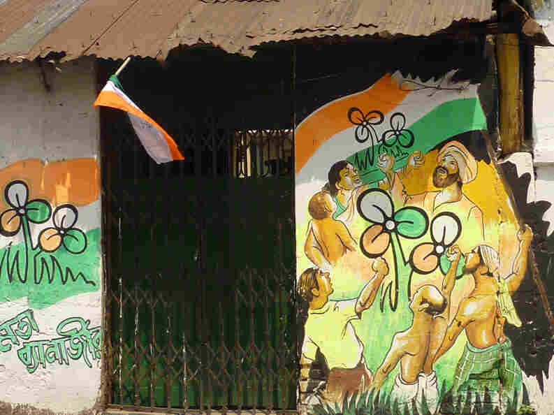 A house on a small side street in Calcutta is adorned with election graffiti. The Trinamool Congress logo looks like a three-leaf clover.  The name of the party's candidate, Mamata Banerjee, is written in Bengali on the lower left.